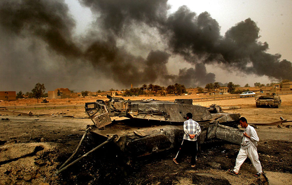 Smoke-filled skies loom over an American tank destroyed during a firefight with Iraqis on the south side of Baghdad, where U.S. forces met heavy resistance en route to the airport on April 6, 2003. Fires were set as a defense tactic.