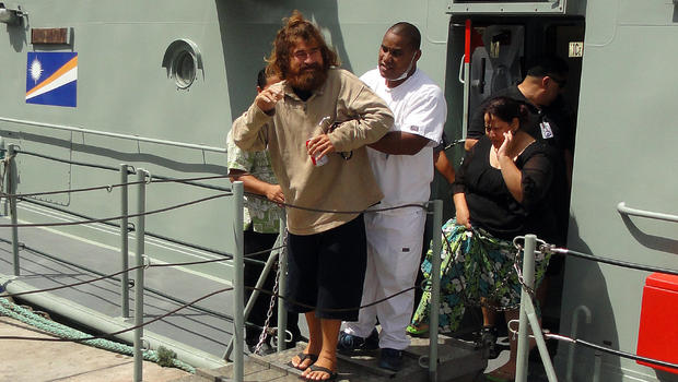 "A castaway from Mexico who identified himself as Jose Salvador Alvarenga steps off the ""Lomor"" Sea Patrol vessel in Majuro, Marshall Islands, with the help of a nurse"